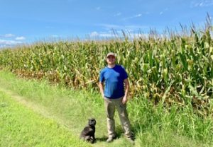 Jesse Todd on a corn field in Chesapeake with his dog, Sneaky Pete.